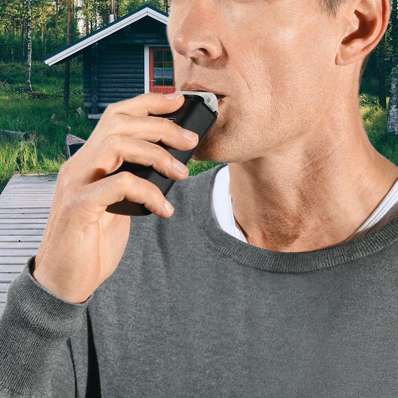 Mies puhaltaa laadukkaaseen Dräger alkotesteriin mitatakseen veren alkoholipitoisuuden. Yksityiseen käyttöön suosittelemme Dräger 4000 alkotesteriä.